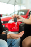 Handshake at car dealership with auto Royalty Free Stock Image