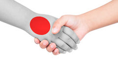 Handshake between a child and Japan. With flags painted on hand in isolated white background Royalty Free Stock Photo