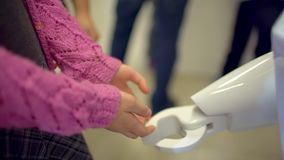 A handshake between a child and a robot. Baby and robot. A handshake between a child and a robot. slow-motion. education, children, technology, science and