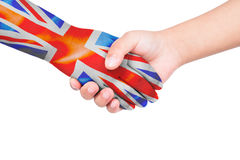 Handshake between a child and United Kingdom. With flags painted on hand in isolated white background Stock Image