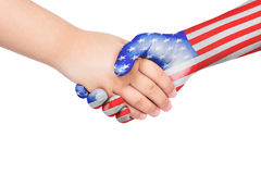 Handshake between a child and United States of America. With flags painted on hand in isolated white background Royalty Free Stock Photography