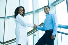 Handshake. Closeup portrait of health care professional or doctor or nurse shaking hands with patient, indoors clinic hospital background Stock Photo