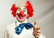 Handshake clown. Clown reaching for handshake with a red nose on a white backround Royalty Free Stock Photo