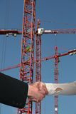 Handshake construction cranes Stock Photos
