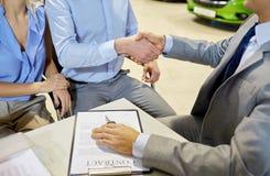 Handshake of customer and car dealer in auto salon Stock Image
