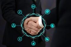 Handshake della donna di affari e dell'uomo d'affari dopo l'affare perfetto con le icone di affari Fotografie Stock