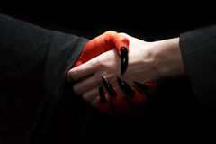 Handshake with Devil. Economycal conceptual image. Male businessman handshake with devil. Dark contrast lighting royalty free stock photos