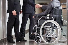 Handshake between disabled man and boss Royalty Free Stock Photos