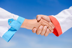 Handshake between doctors over blue sky on sunny Royalty Free Stock Photos