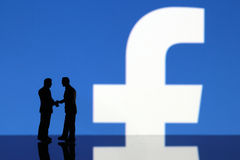 Handshake with Facebook logo. Miniature figures shaking Hands in front of oversized Facebook logo Royalty Free Stock Photos