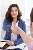 Handshake: Female financial adviser with customer. Royalty Free Stock Photos