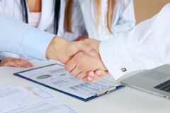 Handshake in front of business people. Stock Image