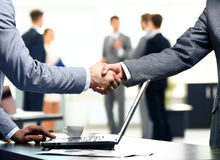 Handshake in front of business people Stock Photo