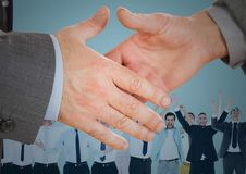 Handshake in front of business people with blue background Royalty Free Stock Photo