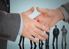 Handshake in front of business people with blue background Royalty Free Stock Image
