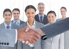 Handshake in front of business people in office against white background Royalty Free Stock Photos