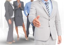 Handshake in front of business people in office. Digital composite of Handshake in front of business people in office Royalty Free Stock Photos