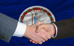 Handshake in front flag ofvirginia. Two businessmen shaking hands after good business investment agreement in front US state flag of virginia Royalty Free Stock Images