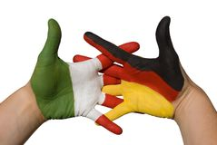 Handshake between germany and italy. One hand with german flag and one hand with italian flag shake hands Royalty Free Stock Photo