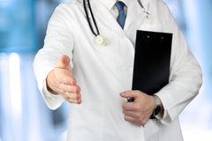 Handshake Gesture from Doctor in  a white  labcoat. And  stethoscope on his sholder Stock Photo