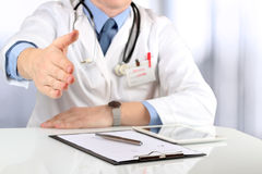 Handshake Gesture from Doctor in a white labcoat and stethoscope Royalty Free Stock Photo