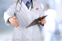Handshake Gesture from Doctor in a white labcoat and stethoscope Royalty Free Stock Photography