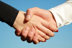 Handshake of the girl and men on blue sky Stock Photo