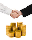 Handshake and gold coins Stock Photo
