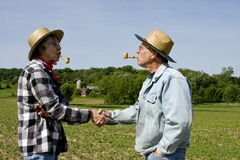 Handshake greeting. Two farmers shaking hands wearing straw hats standing outside on a field Stock Photography