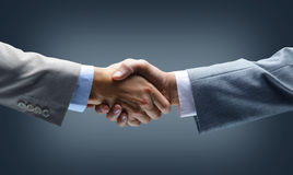 Handshake - Hand holding on. Black background Stock Image