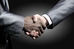 Handshake - Hand holding on black Royalty Free Stock Image