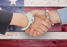 Handshake with handcuffs against wooden american flag background royalty free stock photography