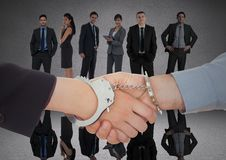 Handshake with handcuffs in front of business people in grey room Royalty Free Stock Photos