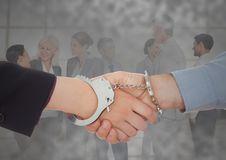 Handshake with handcuffs in front of business people with grunge overlay Royalty Free Stock Images