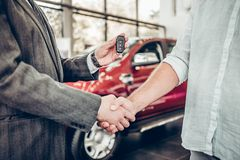 Handshake and handing over the keys to the car by the salon consultant to the buyer royalty free stock images