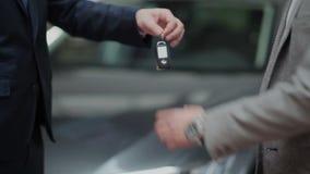 Handshake and handing over the keys. Young guy buying a car from a dealer. Handshake between buyer and seller. Car seller hands over the keys to the buyer stock video