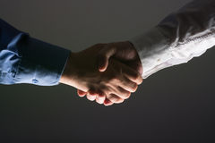 Handshake Handshaking in dark with low light Stock Photography