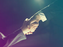 Handshake Handshaking on light and dark Stock Image