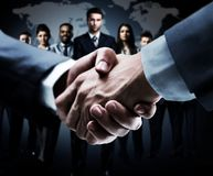 Handshake on the background group of business people in dark colors Royalty Free Stock Images