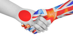 Handshake between Japan and United Kingdom. With flags painted on child`s hands in isolated white background royalty free stock photography
