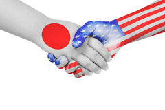 Handshake between Japan and United States of America. With flags painted on child`s hands in isolated white background stock photos