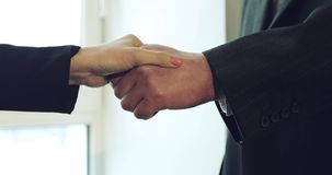 Handshake with the left hand. A beautiful business woman handshaking an old man stock video footage