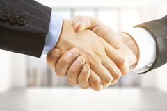 Handshake in a light room Royalty Free Stock Image