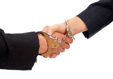 Handshake linked with handcuffs Stock Images