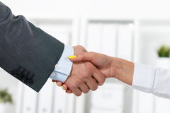 Handshake. Male and female handshake in office. Businessman in suit shaking woman's hand. Serious business and partnership concept. Partners made deal and sealed Stock Image