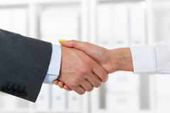 Handshake. Male and female handshake in office. Businessman in suit shaking woman's hand. Serious business and partnership concept. Partners made deal and sealed Stock Photography