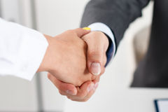Handshake. Male and female handshake in office. Businessman in suit shaking woman's hand. Serious business and partnership concept. Partners made deal and sealed Royalty Free Stock Photography