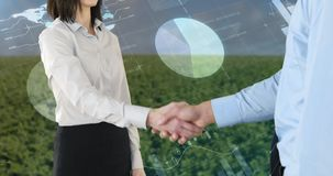 Handshake between a man and a woman 4k. Close up of a handshake between a man and a woman wearing corporate attire with a background of a wide field filled with stock footage