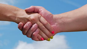 Handshake. A man and woman shaking hands on blue sky background