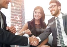 Handshake Manager and the client at a meeting in the office lobby. The concept of partnership stock image